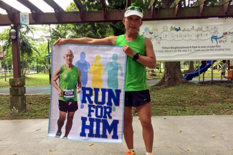 Sports trainer Ng See Chye holds a banner of his father